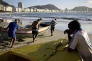 Fischer schieben an der Copacabana ihr Boot ins Meer. (Bild: AFP)