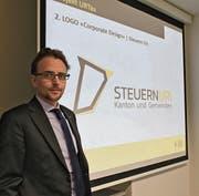 Finanzdirektor Urs Janett stellt das neue Logo vor, das von nun an für alle Schriftstücke rund um die Steuern bei Kanton und Gemeinden verwendet wird. (Bild: Markus Zwyssig (Altdorf, 29. März 2018))