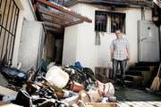 «Steihuis»-Wirt Daniel von Rotz steht fassungslos vor dem zertrümmerten Material, das aus dem Lager hinter ihm geborgen wurde. (Bild Corinne Glanzmann)