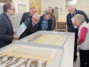 Staatsarchivar Hans Jörg Kuhn (links) bei einer Führung zusammen mit Besuchern, die über die sehr gut erhaltenen historischen Dokumente staunen. (Bild: Paul Gwerder (Altdorf, 18. November 2017))