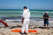 28. August 2015: Im libyschen Zuwara ziehen Rettungskräfte Leichen aus dem Meer und verpacken sie in Leichensäcke. Die Flüchtlinge starben, nachdem zwei Schlepper-Boote gekentert waren. (Bild: AP/Giannis Papanikos)