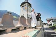 Drei 700-jährige Kirchenglocken wurden für 115'000 Franken aufwendig saniert. Nun kehrten sie nach Spiringen zurück. Bevor sie in den Kirchturm gehievt wurden, segnete Pfarrer Jan Strancich die Glocken ein. (Bild: Urs Hanhart (Spiringen, 22. August 2017))