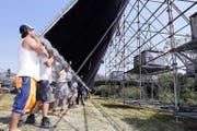 Die Tribüne aufzubauen, kostete die Arbeiter gestern einiges an Kraft und Schweiss (oben). Die Leinwand zu heben, war leichter (unten). (Bilder Werner Schelbert)