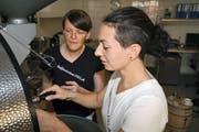 Röstmeisterin Sarah Bürgi (rechts) mit Geschäftspartnerin Susanne Gruss an der Röstmaschine. (Bild Marion Wannemacher)