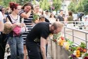 Eine Frau weint, während ein Mann beim Tatort Blumen niederlegt. (Bild: AP/Sebastian Widmann)