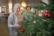 Berta Risi (links) und Frieda Stöckli schmücken im Alterswohnheim Buochs den Christbaum. (Bild: Corinne Glanzmann (Buochs, 20. Dezember 2017))