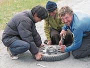 Monika Estermann und Robert Spengeler auf Reisen: in Bolivien (links), Indien (oben rechts) und beim Reifenwechsel (unten rechts). (Bilder: PD)
