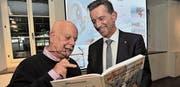 Autor Martin Weiss (links) und der Urner Landammann Beat Jörg schmökern im neuen Comic-Band «Die Munggenstalder in der Teufelsschlucht». (Bild: Urs Hanhart (Altdorf, 27. April 2017))