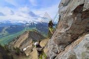 Arbeiter befestigen Armierungseisen am Felsen in luftiger Höhe über dem Gipfelrundweg. (Bild Christian Perret)
