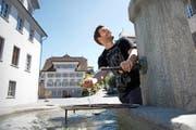 Der Stanser Brunnenmeister Christoph Scheuber beim oberen Dorfbrunnen neben dem Winkelrieddenkmal. (Bild Corinne Glanzmann)
