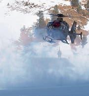 Die Besatzung des EC-635-Helikopters, der auf der Älggialp zum Landen inmitten des aufgewirbelten Schnees ansetzt. (Bild: Schweizer Armee / VBS)