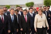 Die deutsche Bundeskanzlerin Angela Merkel (rechts), der türkische Premierminister Ahmet Davutoglu (mitte, rote Krawatte) und der Präsident des Europarats Donals Tusk (dritter von links, blaue Krawatte) in Gaziantep in der Türkei. (Bild: Steffen Kugler/German Federal Government Handout)