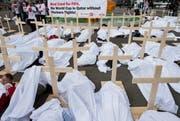 Gewerkschaftsaktivisten unter Leichentüchern: Mit ihrem Protest vor dem Hallenstadion erinnern sie an die vielen Toten auf den Baustellen der WM in Katar. (Bild: Keystone / Ennio Leanza)