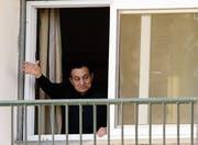 Der abgesetzte Autokrat Hosni Mubarak winkt seinen Anhängern anlässlich seines 87. Geburtstags aus dem Fenster des Militärspitals Maadi in Kairo zu. (Bild: Amr Nabil/AP (Kairo, 4. Mai 2015))