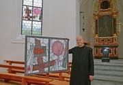 Der Engelberger Pfarrer Pater Patrick Ledergerber mit einer der vier Holztafeln von Pater Karl Stadler. (Bild: PD)