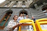 Silvia Wäspe wirft den Brief an Postchefin Susanne Ruoff ein. Dies sekundiert von Stephan Huber, Fredy Weller und Fritz Meier (von links). (Bild Stefan Kaiser)