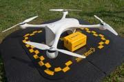 Eine Drohne wird mit einem Paket bestückt, das Laborproben enthält. (Bild: Pablo Gianinazzi / Keystone (Lugano, 31. März 2017))