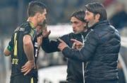 Murat Yakin (rechts), Cheftrainer der Grasshoppers, bespricht sich mit Verteidiger Milan Vilotic, während sich sein Assistent Hakan Yakin (Zweiter von rechts) um die Offensivspieler kümmert. (Bild: Peter Schneider/Keystone (Thun, 21. September 2017))