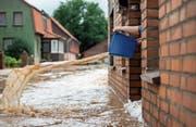 Wasserschöpfen aus der Haustür – Hochwasser nach sommerlichem Extremregen. (Bild: Silas Stein/dpa (Rhüden, 26. Juli 2017))