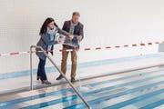 In einem symbolischen Akt giessen Schulpräsidentin Silvia Daucourt und Schulleiter Markus Abry gesegnetes Wasser ins neue Schwimmbecken. (Bild: Edi Ettlin (Oberdorf, 28. Oktober 2017))