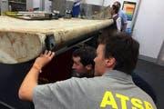 Australische Experten untersuchen ein Trümmerstück. Auf der Pemba Insel wurde ein Trümmerstück eines Flugzeuges gefunden, dass die Behörden dem verschollenen MS370-Flugzeug zuordnen. (Bild: EPA/ATSB AUSTRALIA AND NEW ZEALAND)