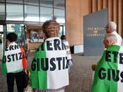 """Verwandte von Asbest-Opfern, eingehüllt in italienische Flaggen mit dem Schriftzug """"Eternit Giustizia"""" (zu deutsch etwa: """"Gerechtigkeit im Eternit-Fall""""), vor dem Turiner Justizpalast. (Archiv) (Bild: Keystone/EPA ANSA/ALESSANDRO DI MARCO)"""