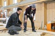 Projektleiter Krystian Grzybek (rechts) zeigt Daniel Albrecht in den Räumen der Holzbaufirma Walter Küng in Alpnach die einzelnen Arbeitsschritte zum fertigen Holzpur-Wandelement.Bild: PD