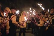Mit einem Fackelzug (links) wird am Dreikönigstag jeweils der neue Heinivater vorgestellt. Der mimt während der Fasnacht den legendären «Heini von Uri», begleitet von den drei Trabanten; rechts, von oben: Teufel, Feuk und Lälli. B (Bilder: Corinne Glanzmann)