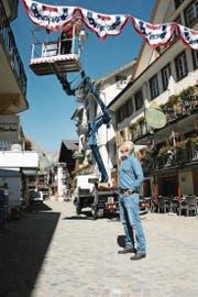 Bereit für das Freilichtspektakel: Tourismusdirektor Frédéric Füssenich schaut zu, wie Martin Amstutz vom Werkhof die erste Girlande in der Dorfstrasse montiert. (Bild: Philipp Unterschütz (Engelberg, 5. Juli 2017))