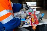 Ein Mitarbeiter des Werkhof der Stadt Luzern durchsucht den Güsel, der illegal entsorgt wurde. Er sucht nach Spuren des Güselsünders. (Bild: Dominik Wunderli (Luzern, 31. Januar 2013))