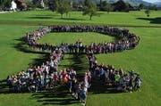 """Die Schule Giswil hat in diesem Jahr das Motto """"Wurzlä schlah, wachsä lah"""". Im Bild: Die Schülerinnen und Schüler sowie die die Co-Schulleiter Isabelle Wyss und Thomas Heiniger stellten sich symbolisch zu einem grossen Baum auf. (Bild: Neue OZ/Birgit Scheidegger)"""