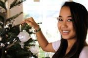 Lindsey Chun aus Hawaii hilft, den Christbaum ihrer Obwaldner Gastfamilie zu schmücken. (Bild Anna Burch)