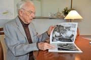Arnold Odermatt blättert in einem seiner Bildbände. (Bild Martin Uebelhart)