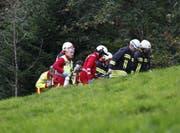 Der Schwerverletzte wird zum Helikopter gebracht. (Bild: Geri Holdener, Bote der Urschweiz)