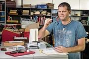 Tobias Schwarzentruber begutachtet vorsichtig eine der Briefmarken, die er in seinem Laden verkauft. (Bild: Philipp Schmidli (Sursee, 7. Dezember 2017))