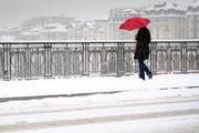 Eine Person, die sich mit einem Schirm vor dem Schnee schützt. (Symbolbild) (Bild: Laurent Gillieron / Keystone (Lausanne, 1. März 2018))