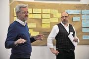 Projektleiter Patrick Deicher (rechts) und Moderator Stefan Käppeli nehmen die auf farbigen Karten notierten Inputs zur Gemeindefusion Bauen-Seedorf auf. (Bild: Urs Hanhart (Seedorf, 16. März 2018))