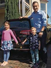 Marco Stampfli mit seiner Tochter Lena und Sohn Liam vor seinem Auto mit Uristier, mit dem er auch in Australien auf seine Wurzeln aufmerksam macht. (Bild: PD (Sydney, 27. August 2017))
