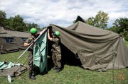 Angehörige der Armee stellen Zelte zur vorübergehenden Unterbringung von Flüchtlingen in Lyss auf. (Bild: Keystone / Peter Schneider)