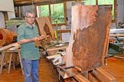 Der Lungerer Bildhauer Karl Imfeld hält ein Modell seiner Bartheke in den Händen. Daneben entsteht das Kunstwerk aus dem Holz eines 200-jährigen Riesen-Mammutbaums. (Bild Robert Hess)