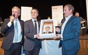 Bundesrat Ignazio Cassis (Mitte) erhält von Urs Frei, Präsident der FDP Toggenburg, einen Schlorzifladen mit Porträt und ein Panorama-Messer mit der Silhouette der Churfirsten. Links im Bild Moderator Sven Bradke. (Bild: Ralph Ribi)