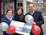Bankleitungsmitglied Benjie Egloff bei der Checkübergabe an Marianne Wright und Désirée Bachofen vom OK-Team der Kinderfasnacht Nesslau-Neu St. Johann. (Bild: PD)