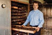 Türe auf, «Schublade» raus: Dörrmeister Thomas Oeler zieht eine Hurde voller Dörrbirnen aus seinem alten Holzofen. (Bild: Luca Linder)