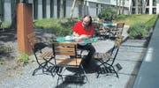 In Gedanken versunken sitzt Lebenskünstler Mark Riklin im Innenhof des Lagerhauses und hält in seinem Logbuch neue Ideen fest. (Bild: bra)