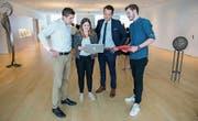 Maurin Büche, Anina Angehrn und Dimitri Sonderegger mit Bankleiter Aldo Kopp in der Raiffeisen-Filiale Niederuzwil. (Bild: PD)