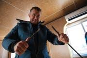 Regisseur Beni Giger zeigt eines der defekten Glasfaserkabel. (Bild: PD)