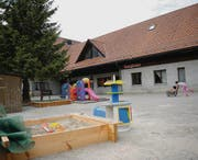 Alltag in der Gruppenunterkunft für Asylsuchende: Während die Kinder auf dem umzäunten Parkplatz spielen, hat eine erwachsene Person Aufsicht. Die anderen sind mit der Reinigung oder Kochen beschäftigt. (Bild: Olivia Hug)