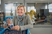 Andrea Berlinger Schwyter zeigt die manipulationssicheren Flaschen für Dopingkontrollen. Im Hintergrund arbeitet ein Spezialroboter. (Bilder: Ralph Ribi)