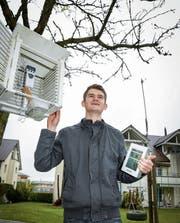 Florian Zangl im Garten vor seiner elterlichen Wohnung. Die Daten des Thermometers im Wetterhüttchen und vom Windmesser auf der Schaukel werden per Funk an die Wetterstation übermittelt. (Bild: Ralph Ribi)