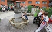 Marina und Silvan bestückten mit Hilfe ihrer Urgrossmutter Hanni Brunner den Brunnen mit Bällen. (Bild: Cecilia Hess-Lombriser)